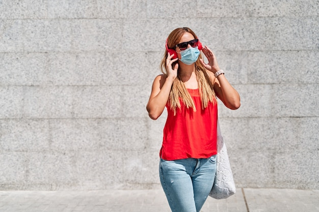 Young woman with a mask listening to music in the city