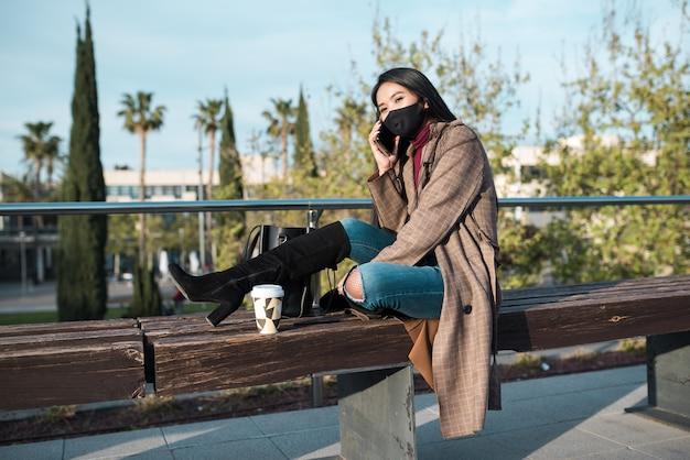 ベンチに座って電話で話しているマスクを持つ若い女性。彼女は黒いハイブーツを履いていて、ベンチに寄りかかってコーヒーカップを持っています
