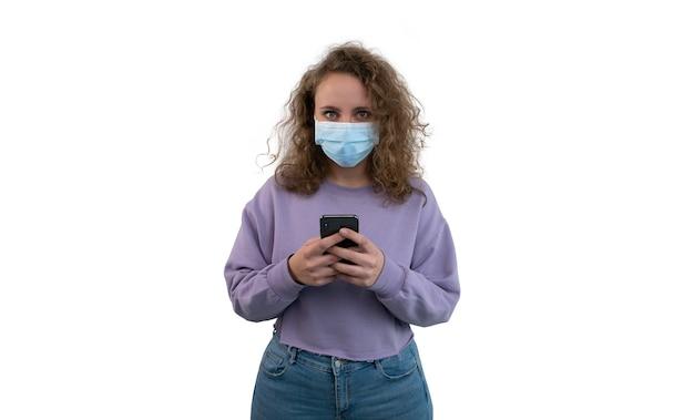 코 비드를 방지하기 위해 마스크를 가진 젊은 여자는 고립 된 그녀의 스마트 폰에 입력합니다