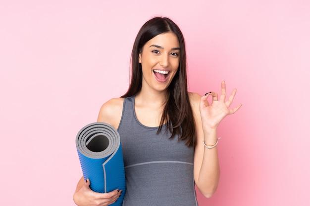 指でokサインを示すピンクのマットを持つ若い女性
