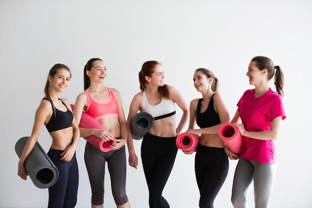Молодая женщина с ковриками для йоги в тренажерном зале перед тренировкой