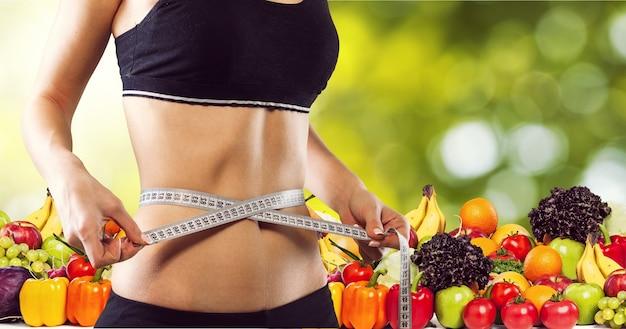 健康食品の背景に巻尺を持つ若い女性