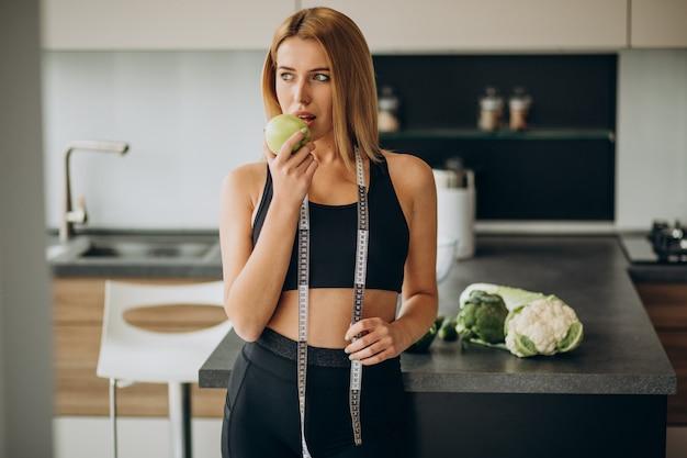 キッチンで測定テープを持つ若い女性