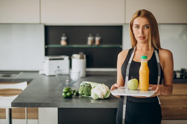 Giovane donna con nastro di misurazione in cucina