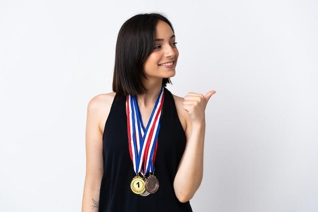 Молодая женщина с медалями, изолированными на белой стене, указывая в сторону, чтобы представить продукт