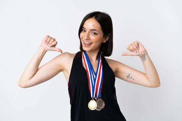 Молодая женщина с медалями, изолированными на белой стене, гордая и самодовольная