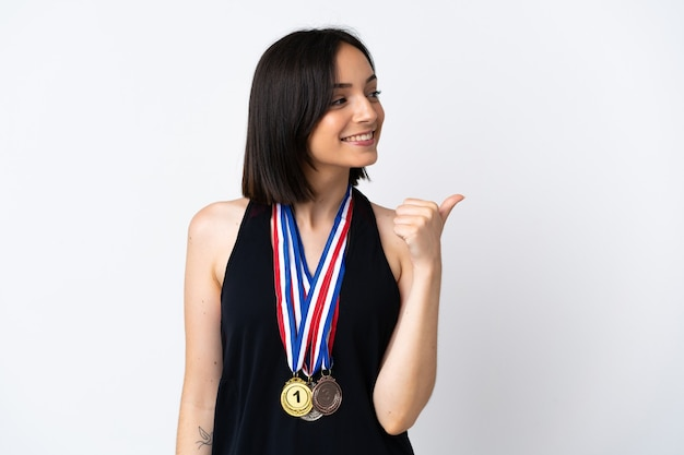Young woman with medals isolated on white wall pointing to the side to present a product