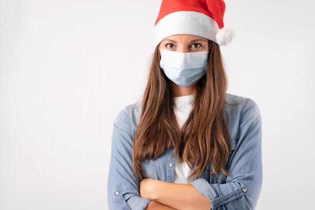 의료 마스크와 흰색 바탕에 산타 모자와 젊은 여자. 격리에 크리스마스. 고품질 사진