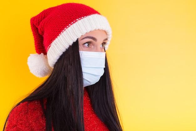 의료 마스크와 흰색 바탕에 산타 모자와 젊은 여자. 격리에 크리스마스.