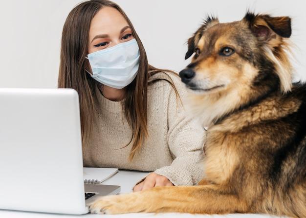 Молодая женщина с медицинской маской играет со своей собакой