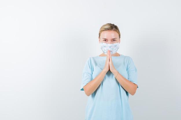 Giovane donna con una maschera medica che prega