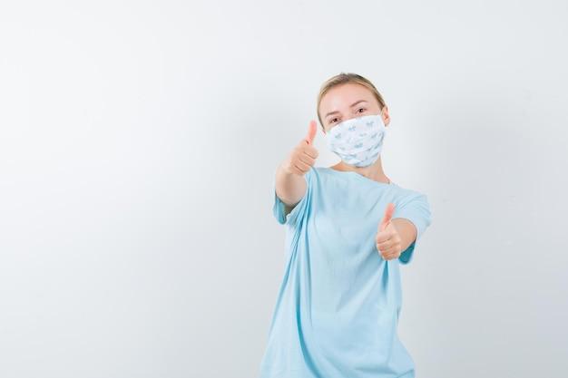 Giovane donna con una maschera medica che mostra i pollici in su
