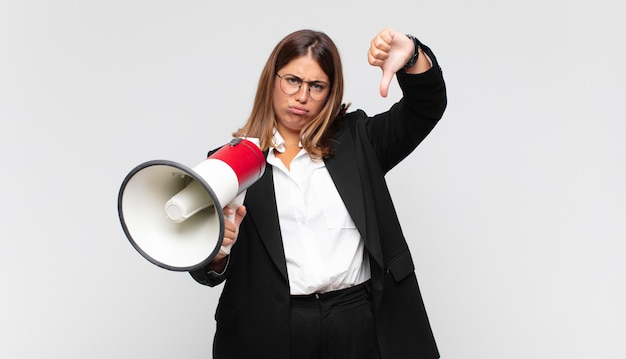Young woman with a megaphone feeling cross, angry, annoyed, disappointed or displeased, showing thumbs down with a serious look