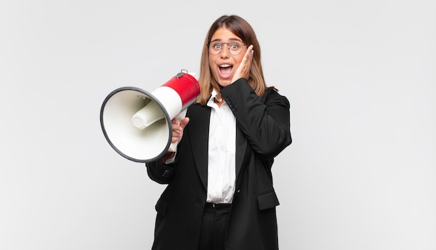Young woman with a megaphone feeling happy, excited and surprised, looking to the side with both hands on face