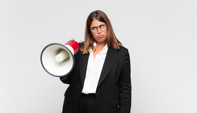 Young woman with a megaphone feeling sad, upset or angry and looking to the side with a negative attitude, frowning in disagreement