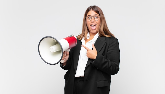 Young woman with a megaphone looking excited and surprised pointing to the side and upwards to copy space