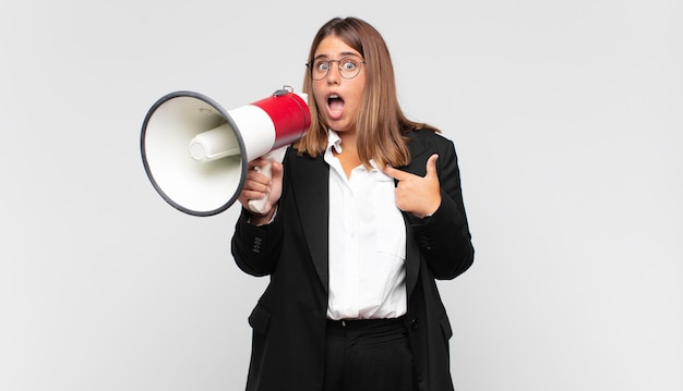 Young woman with a megaphone looking shocked and surprised with mouth wide open, pointing to self