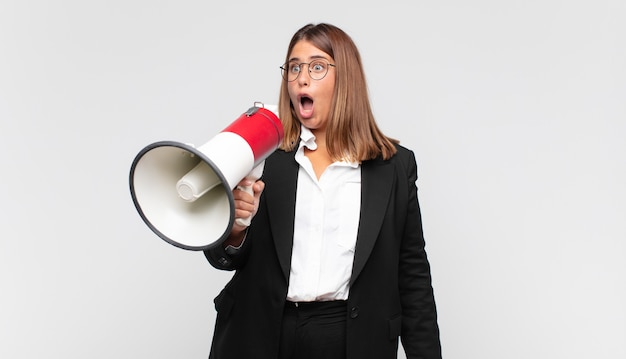 Young woman with a megaphone looking very shocked or surprised, staring with open mouth saying wow