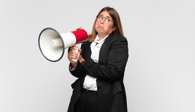Young woman with a megaphone shrugging, feeling confused and uncertain, doubting with arms crossed and puzzled look