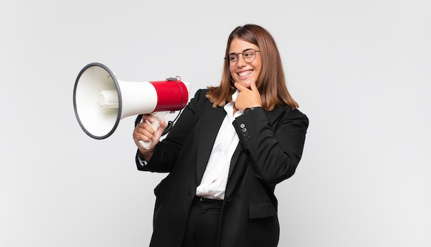 Young woman with a megaphone smiling with a happy, confident expression with hand on chin, wondering and looking to the side