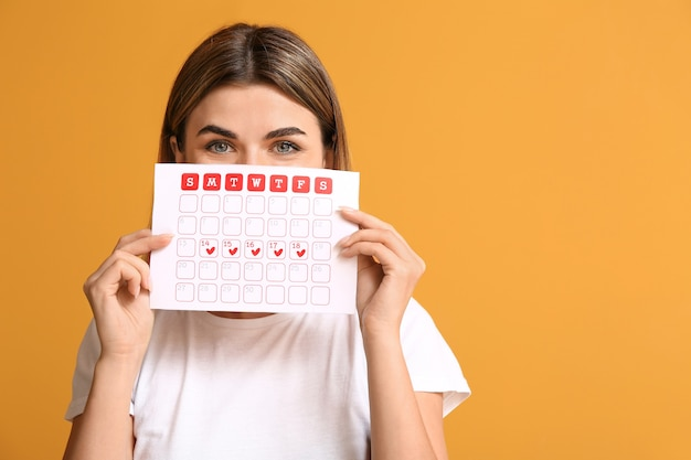 Young woman with menstrual calendar on color surface