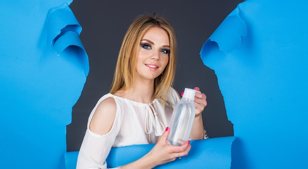 ミセル水を持つ若い女性。フェイストニックと幸せな女の子。メイク落とし。ビューティートリートメント。化粧品の広告。