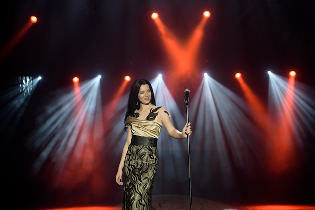Young woman with microphone in hand on entertainment event.