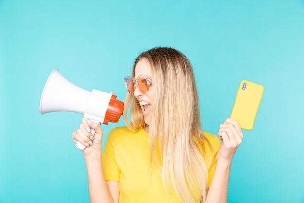 휴대 전화 및 색상에 확성기와 젊은 여자.