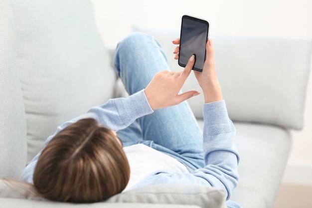 自宅で携帯電話を持つ若い女性