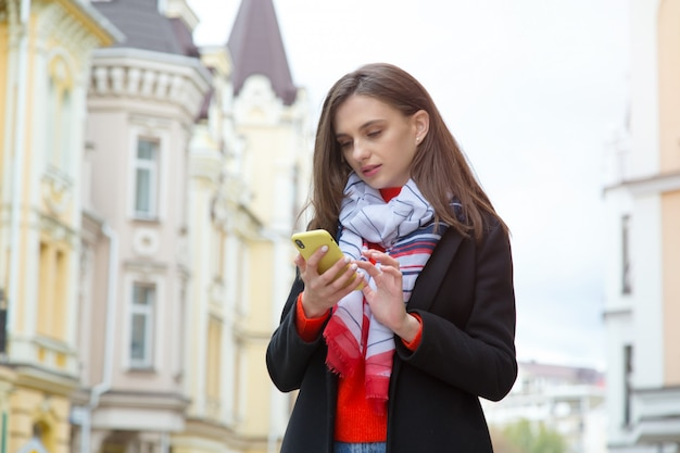 Young woman with a mobile phone on a city
