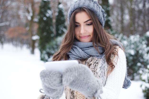 冬の携帯電話を持つ若い女性