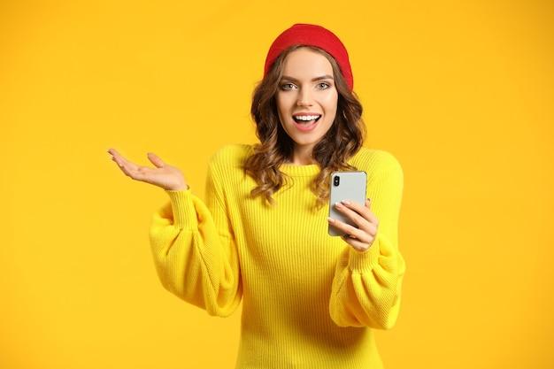 色の携帯電話を持つ若い女性