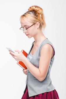 灰色の壁に携帯電話を持つ若い女性