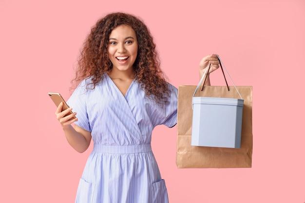 携帯電話、ショッピングバッグ、色の背景のボックスを持つ若い女性