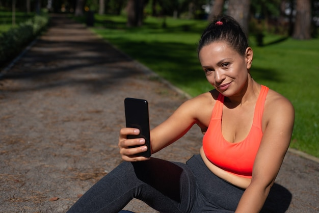 Young woman with mobile phone sits on a walkway in the park and smiles while looking at the camera