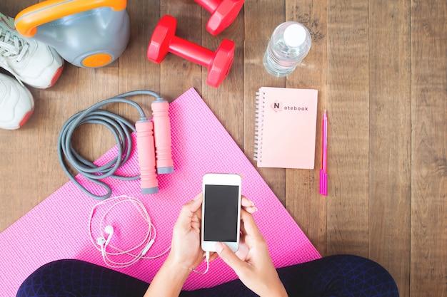 Молодая женщина с мобильного телефона, сидя возле гантели на циновка йоги, вид сверху.
