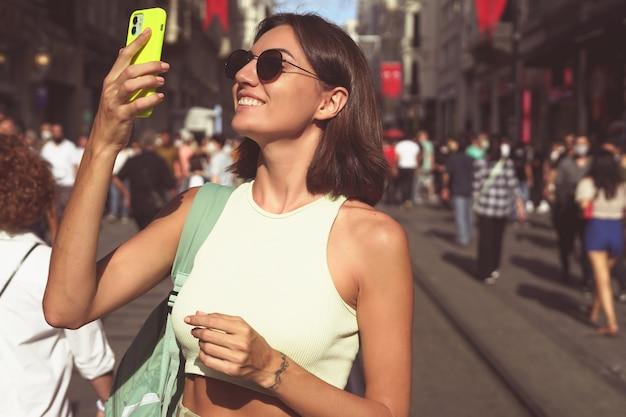 휴대전화를 든 젊은 여성은 도시의 아름다움을 즐기며 행복한 이스탄불의 혼잡한 거리를 여행한다