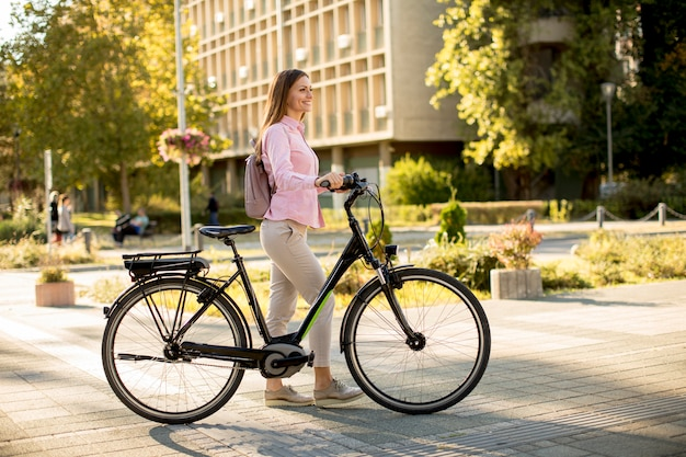 Young woman with modern city electric e-bike clean sustainable urban transportation