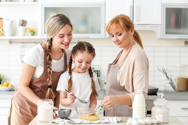 Молодая женщина с матерью и дочерью, готовящей на кухне