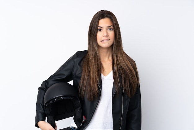Young woman with a motorcycle helmet over isolated white wall having doubts and with confuse face expression