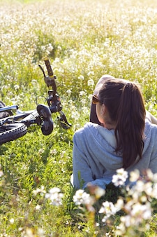 Young woman with mountain bike stretched on the field
