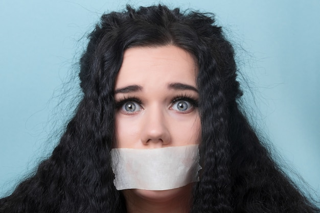 Young woman with mouth and lips sealed in adhesive tape, censored and banned to speak, hostage