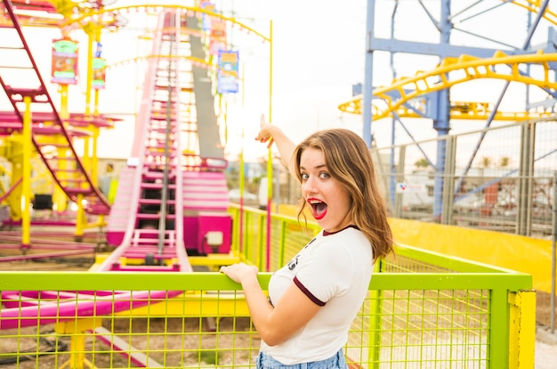 Young woman with mouth open pointing her finger at roller coaster ride
