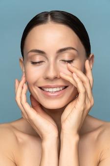 자연스러운 메이크업을 가진 젊은 여성, 머리를 빗질하고, 얼굴에 깔끔한 순수한 피부를 만지고 있습니다.