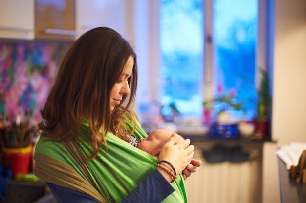 Молодая женщина с новорожденным младенцем в слинге с размытым фоном дома