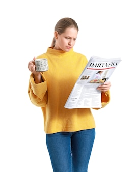 Young woman with newspaper and cup of coffee on white background