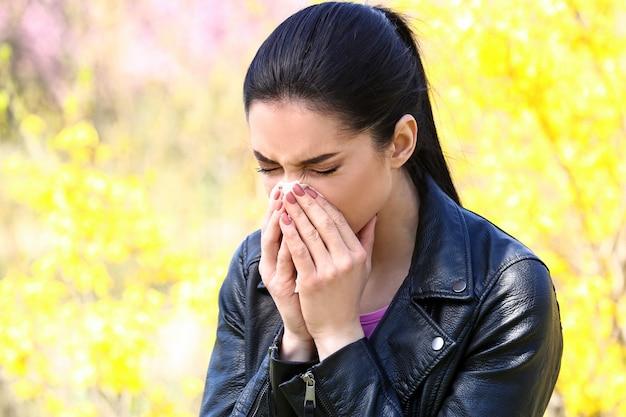 春の日に鼻ワイパーを持つ若い女性