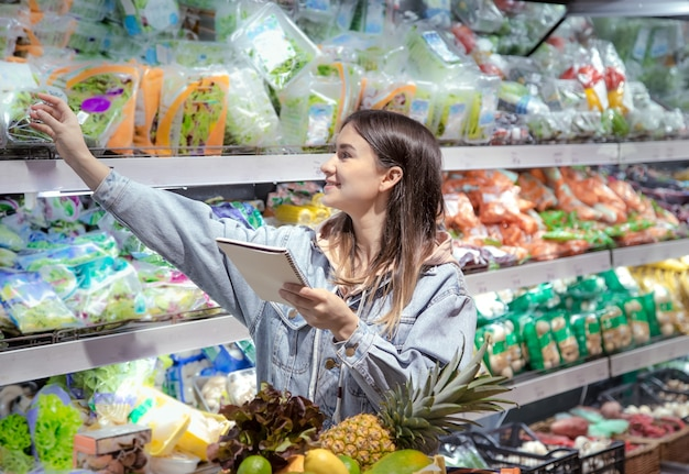 A young woman with a notebook buys groceries in the supermarket