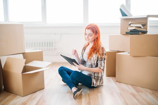 段ボール箱の間の床に座って、新築祝いのノートを持つ若い女性。新しい家への移転