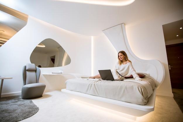 Молодая женщина с ноутбуком сидит, сидя в роскошной квартире